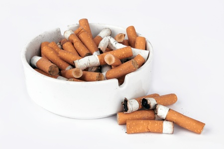 Ashtray full of cigarettes isolated on white photo