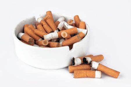 Ashtray full of cigarettes isolated on white photo