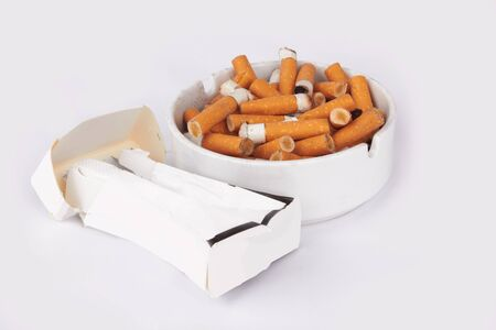 Ashtray full of cigarettes on white  photo