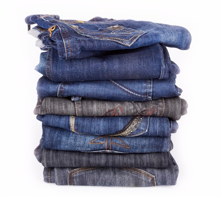 Lot of different jeans close-up isolated on white