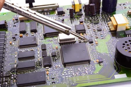 computer micro circuit board with iron soldering and tin wire in electronic laboratory