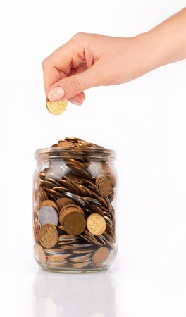 dime: hand put coin jar with coins isolated on white