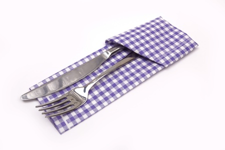 knife and fork on a napkin on the white photo