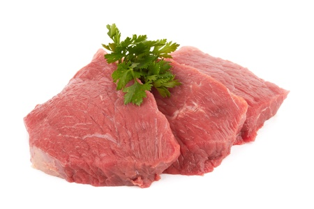 Three round steaks on a white background