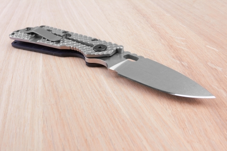 Folding knife on a wooden background photo