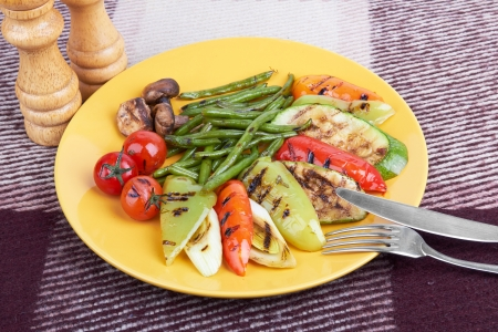grilled vegetables on a yellow platefnd fork fnd knife