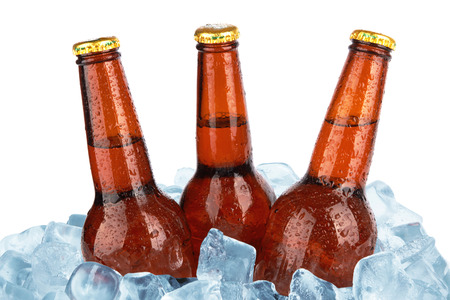 Three beer bottles in ice with condensation isolated on white background photo