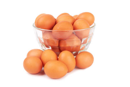 brown eggs in transparent bowl isolated on white  photo
