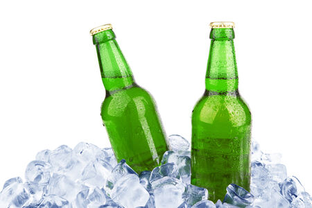 Two bottles of beer on ice isolated on white background  photo