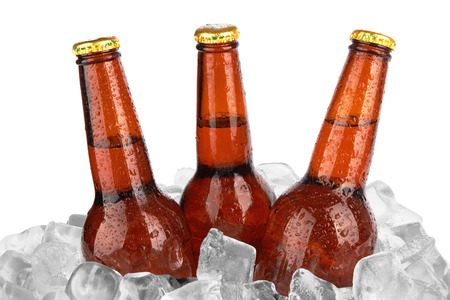 Three beer bottles in ice with condensation isolated on white background