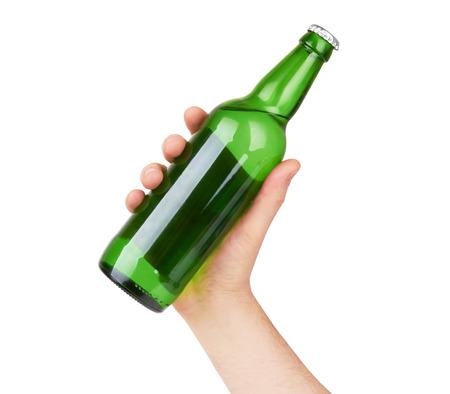 白い背景に分離されたラベルのない緑色のビール瓶を持っている手 写真素材