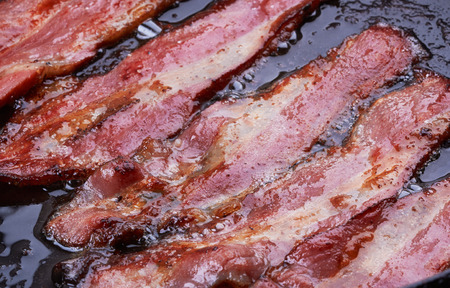 streaky: Bacon strips or rashers being cooked in frying pan