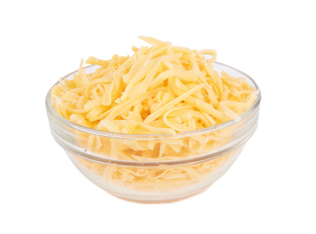 Glass bowl of grated cheese isolated on white