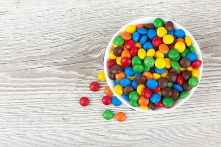 colorful chocolate buttons on a wooden background
