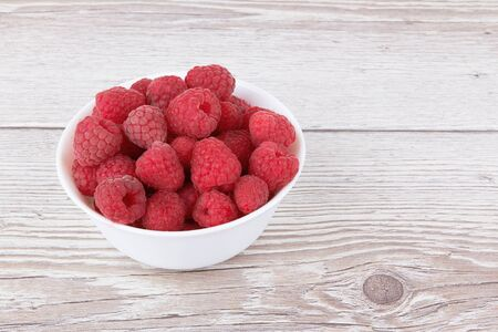 Raspberry fruit closeup isolated on wooden background