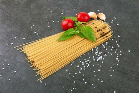 spaghetti on a stone black background with basil