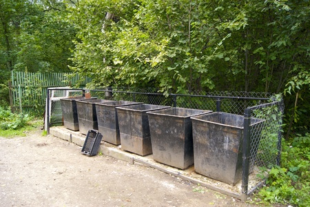 fenced playground in the park with a trash container