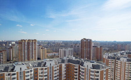 The view from the window of a tall building on a cityscape. Sunny weather and blue sky. Dense buildings