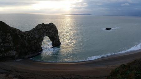 durdle door: Sunset at Durdle Door natural arch linestone on the Jurassic Coast in Dorset England UK Europe Stock Photo