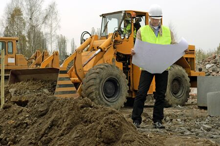 Photo of excavator and architect with plans.