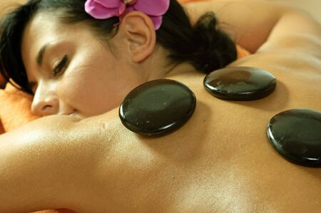 Photo of young woman using stone massage.