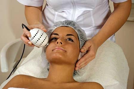 Beautiful young woman getting face massage in spa. photo