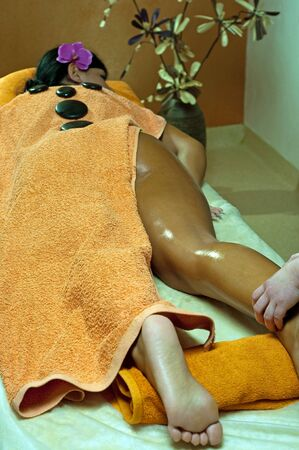 hot rock therapy: Photo of young woman using stone massage.