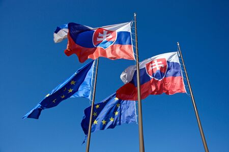Photo of flags of Slovakia and European Union waving on wind
