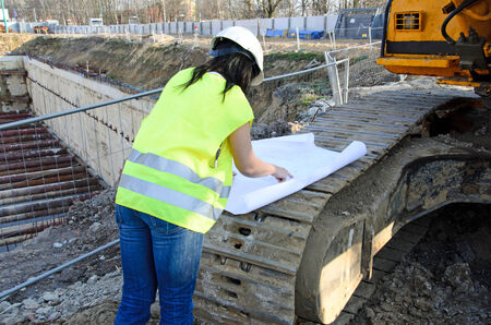 workwoman: a photo of a young woman architect on the building site of the construction project