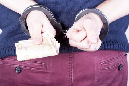 locked in: a picture of a criminal locked in handcuffs trying to bribe