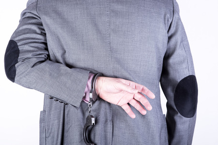 locked in: a picture of a businessman locked in handcuffs