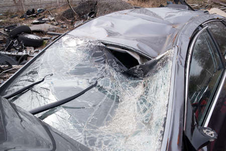 heavily: photo showing the heavily crashed car in a road accident
