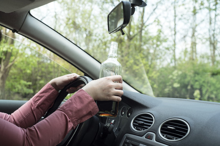 arrest women: picture of woman drinking alcohol in the car.