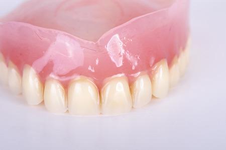 falso: Foto de la dentadura postiza en el fondo blanco Foto de archivo