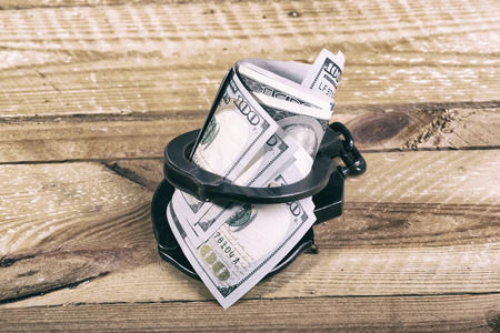 Handcuffs and dollar bills Stock Photo