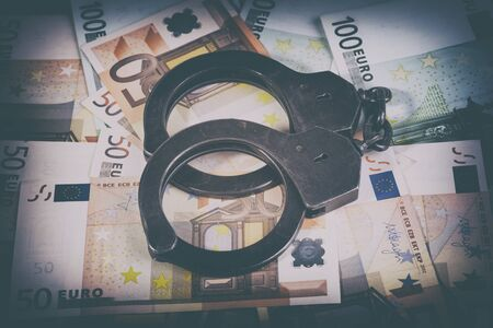 Handcuffs and euro bills