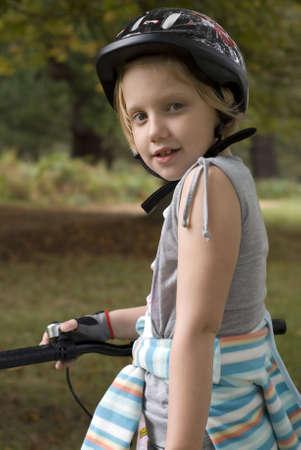 Little girl riding bike wearing helmet. Stock Photo