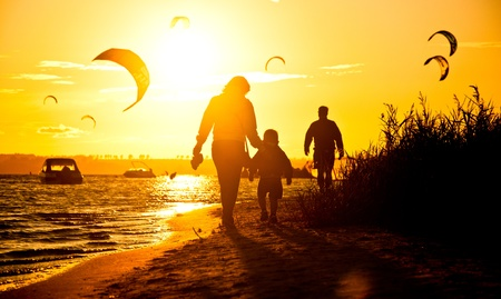 Family walking on coast during sunset