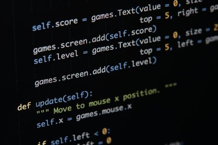 Real Python code developing screen. Programing workflow abstract algorithm concept. Lines of Python code visible under magnifying lens. Stock Photo