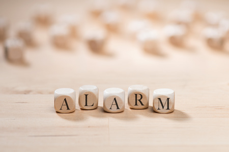 Alarm word on wooden cubes. Alarm concept