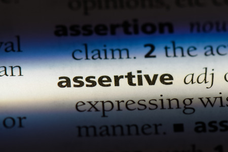 assertive word in a dictionary. assertive concept. Banco de Imagens - 99481198