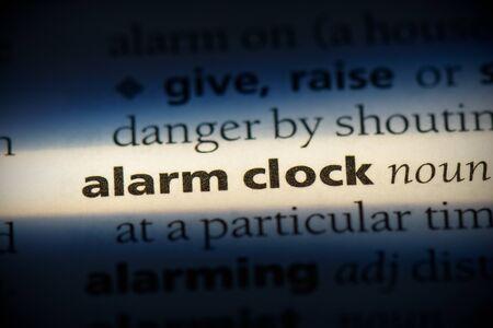 alarm clock word in a dictionary. alarm clock concept, definition.
