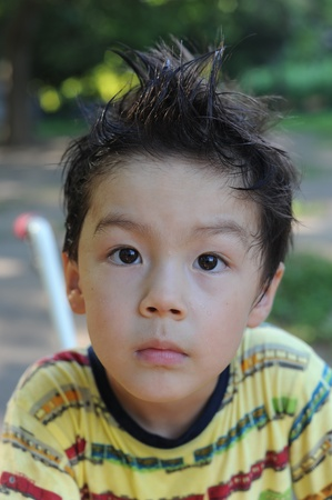 Boy with wet, standing hair and serious look photo