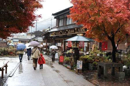 People with umbrellas strolling during rain in autumn