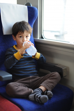 Boy riding a train and drinking soda photo