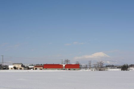 White winter landscape with a village and snow-covered volcano photo