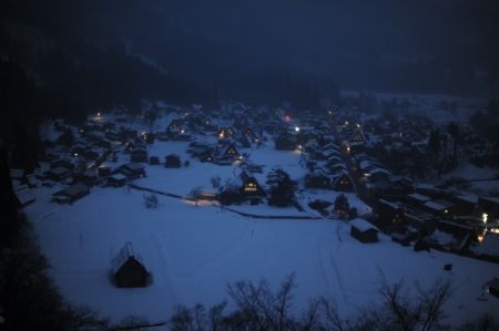 Thatched roof houses covered in snow at night