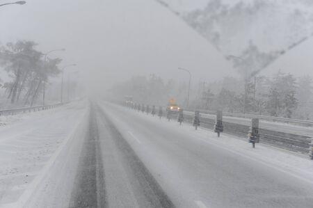 Winterlandschaft mit einer Straße im Schneesturm Standard-Bild