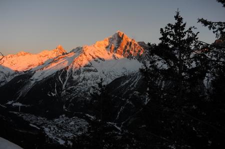 Alpes franceses durante el atardecer con un pueblo en el valle Foto de archivo - 91313935