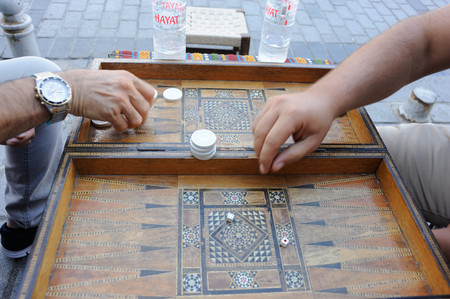 Men playing backgammon board game with an old wooden table, checkers and dice in Turkey Stock Photo